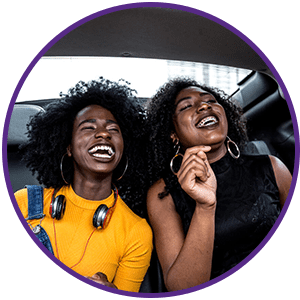 two-young-women-laughing-in-backseats-of-car