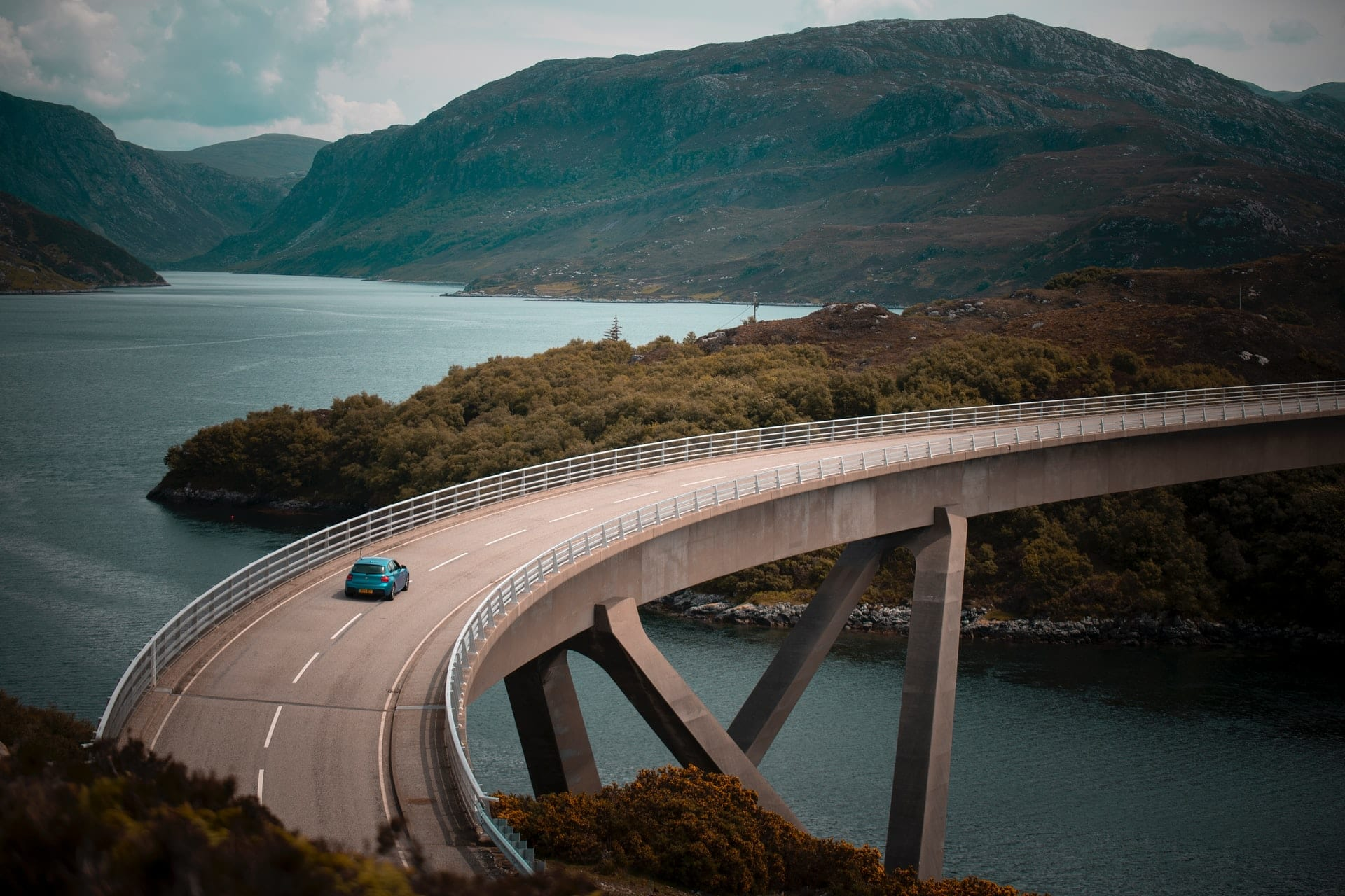 car-driving-across-a-winding-bridge-above-lake-with-mountains-in-background-kylesku-bridge-in-assynt-north-coast-500-scotland-best-scenic-drives-in-uk