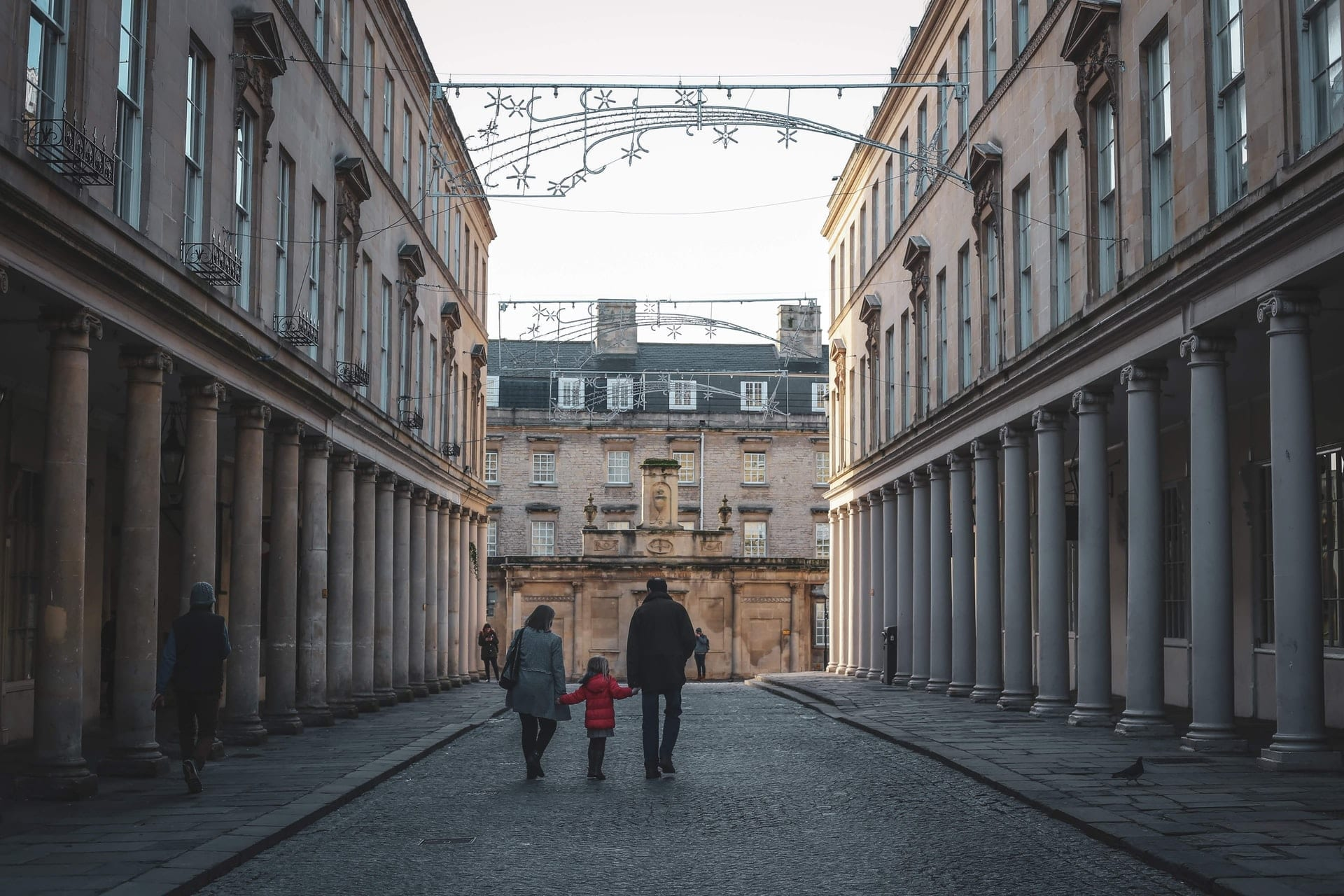 family-walking-down-a-street-in-bath-england-in-december-at-christmas