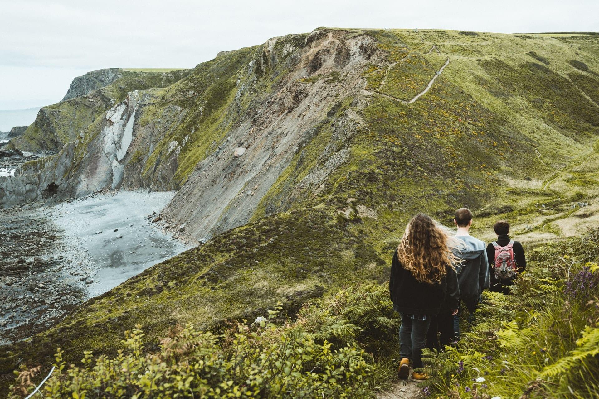 friends-walking-amid-greenery-along-coastal-cliffs-atlantic-highway-cornwall