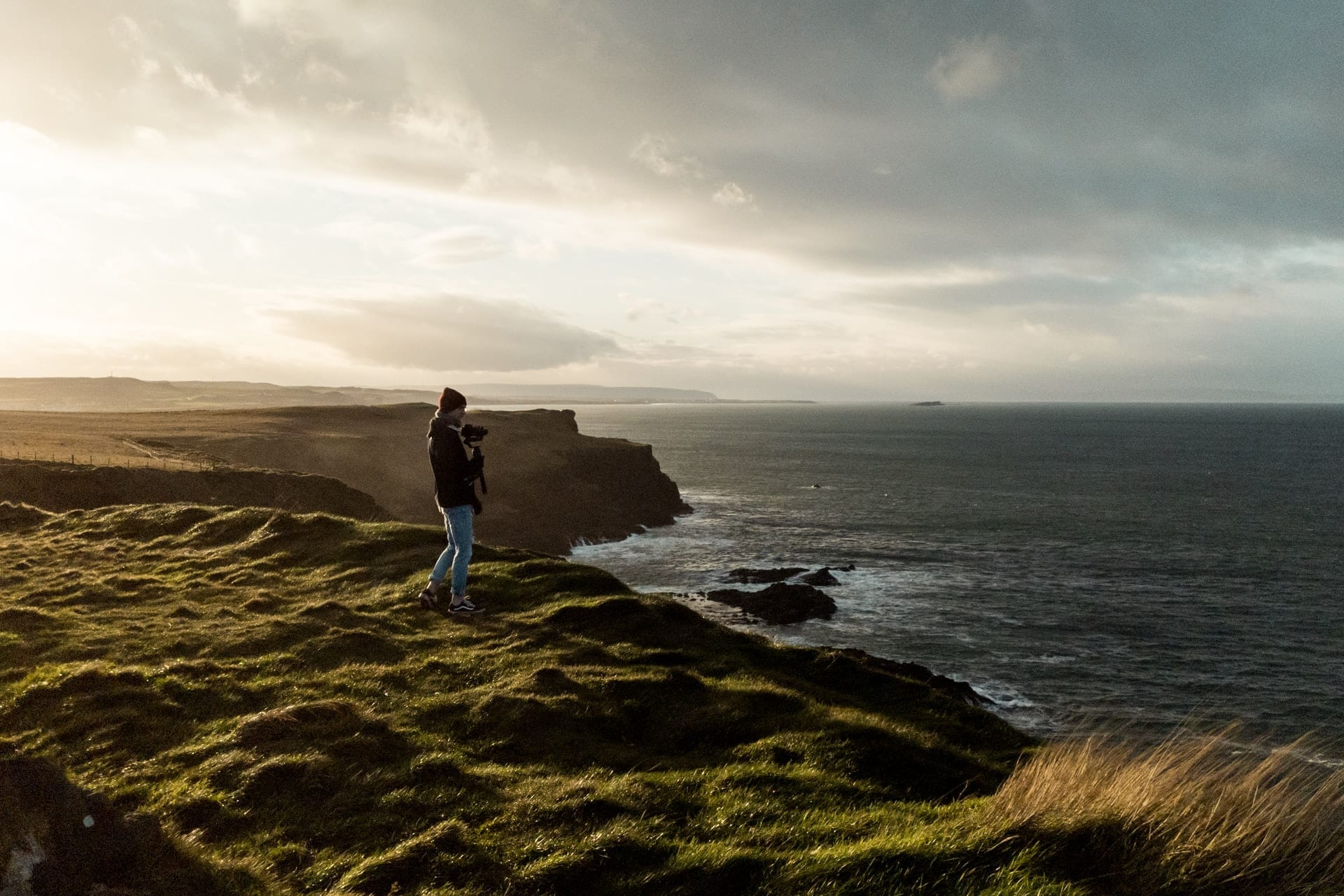 man-holding-camera-walking-along-cliff-by-coast-at-sunset-coastal-causeway-route-northern-ireland