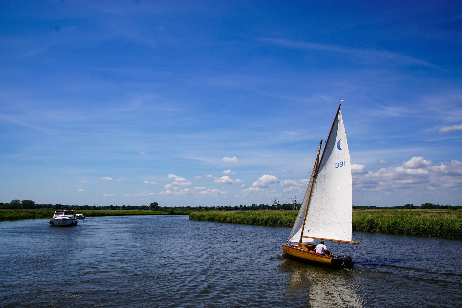 man-in-boat-on-sunny-summer-day-sailing-across-the-norfolk-broads-england