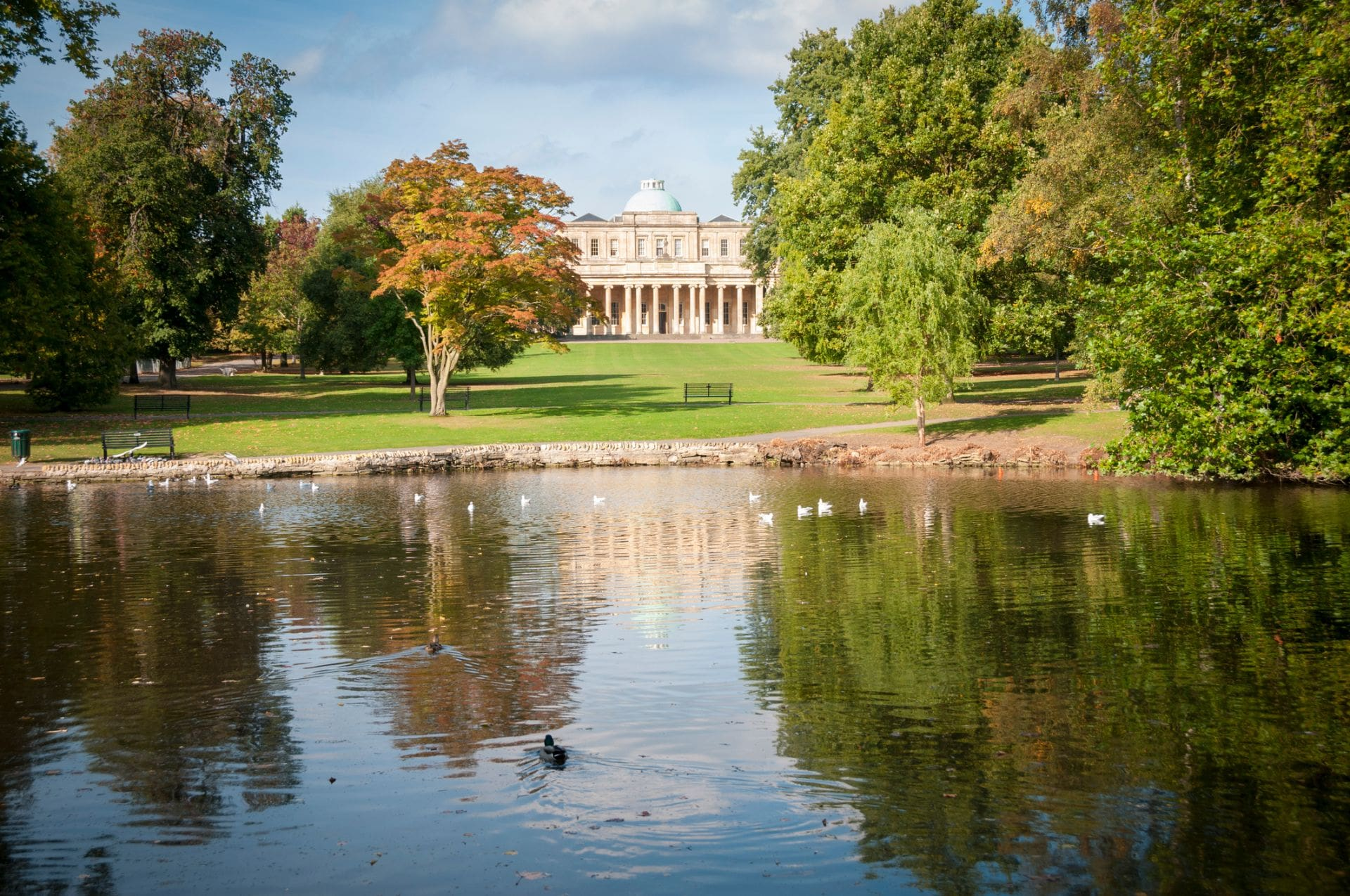 old-historic-building-overlooking-lake-in-autumn-at-pittville-park-in-cheltenham