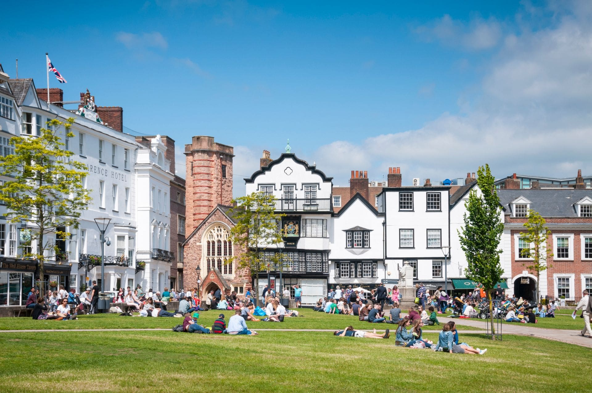 people-laying-on-grass-in-city-centre-in-front-of-cafes-shops-and-hotels-on-sunny-day-exeter-devon