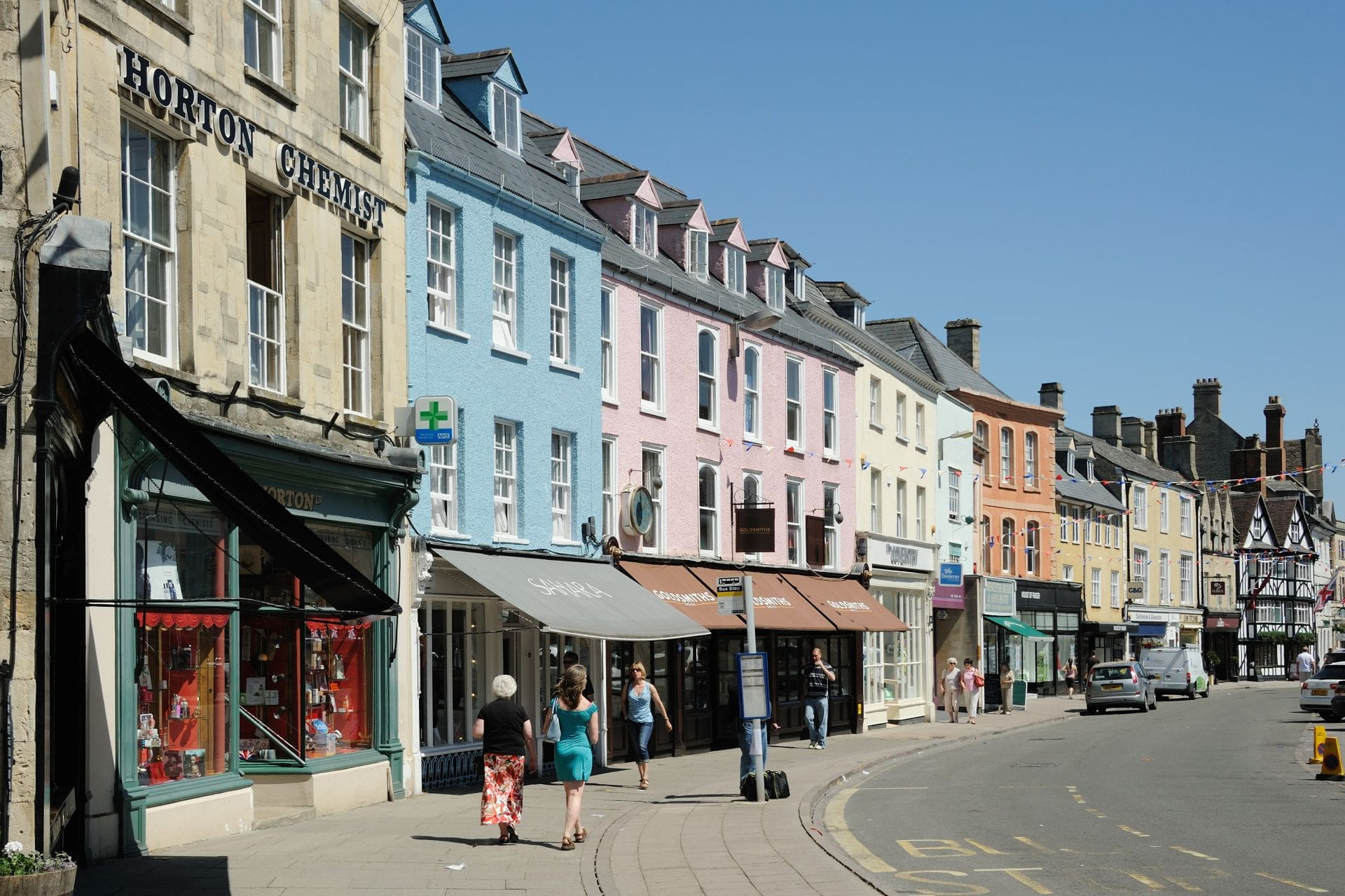 people-walking-down-british-high-street-with-colourful-shops-on-sunny-day-in-cirencester-gloucestershire