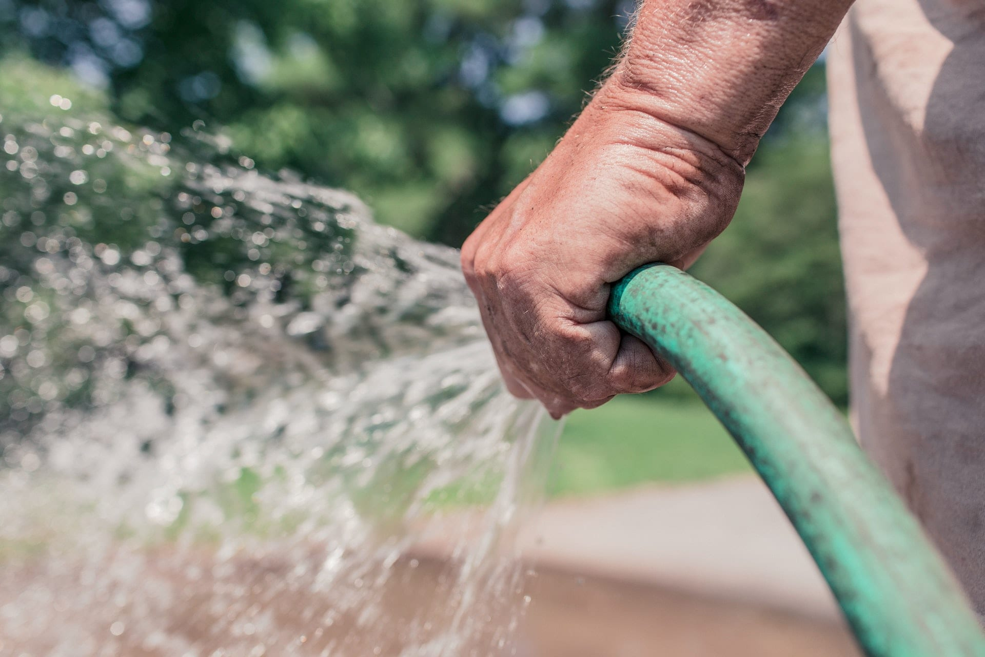 man's-hand-holding-green-hose-with-water-coming-out-of-it