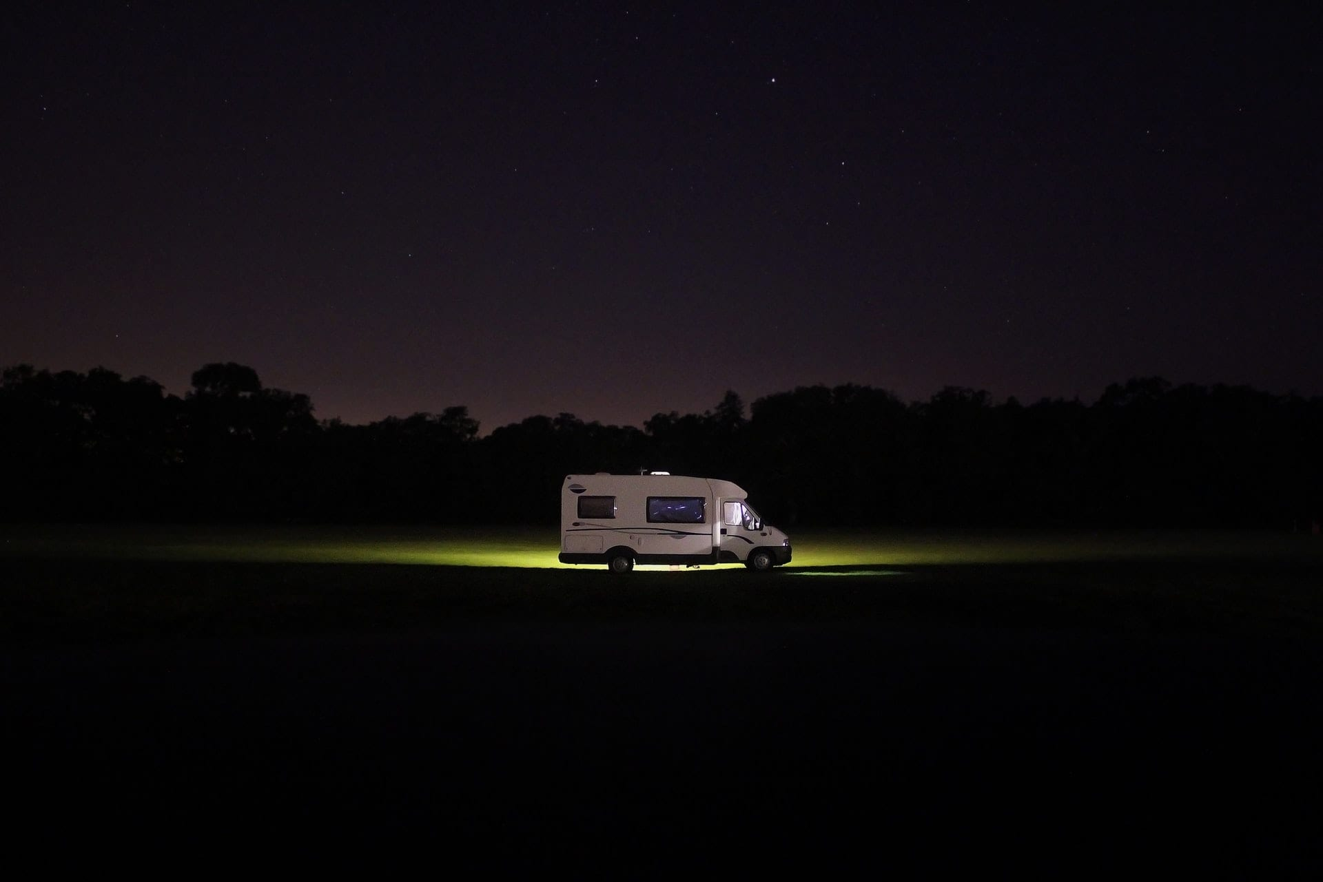 motorhome-lit-up-in-field-at-night-essential-motorhome-accessories