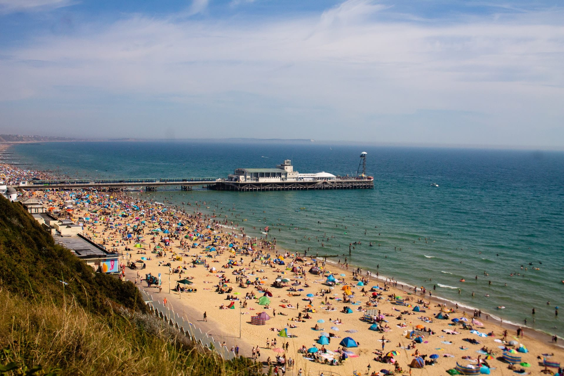 tourists-sunbathing-on-sandy-beach-by-pier-and-sea-in-bournemouth-england