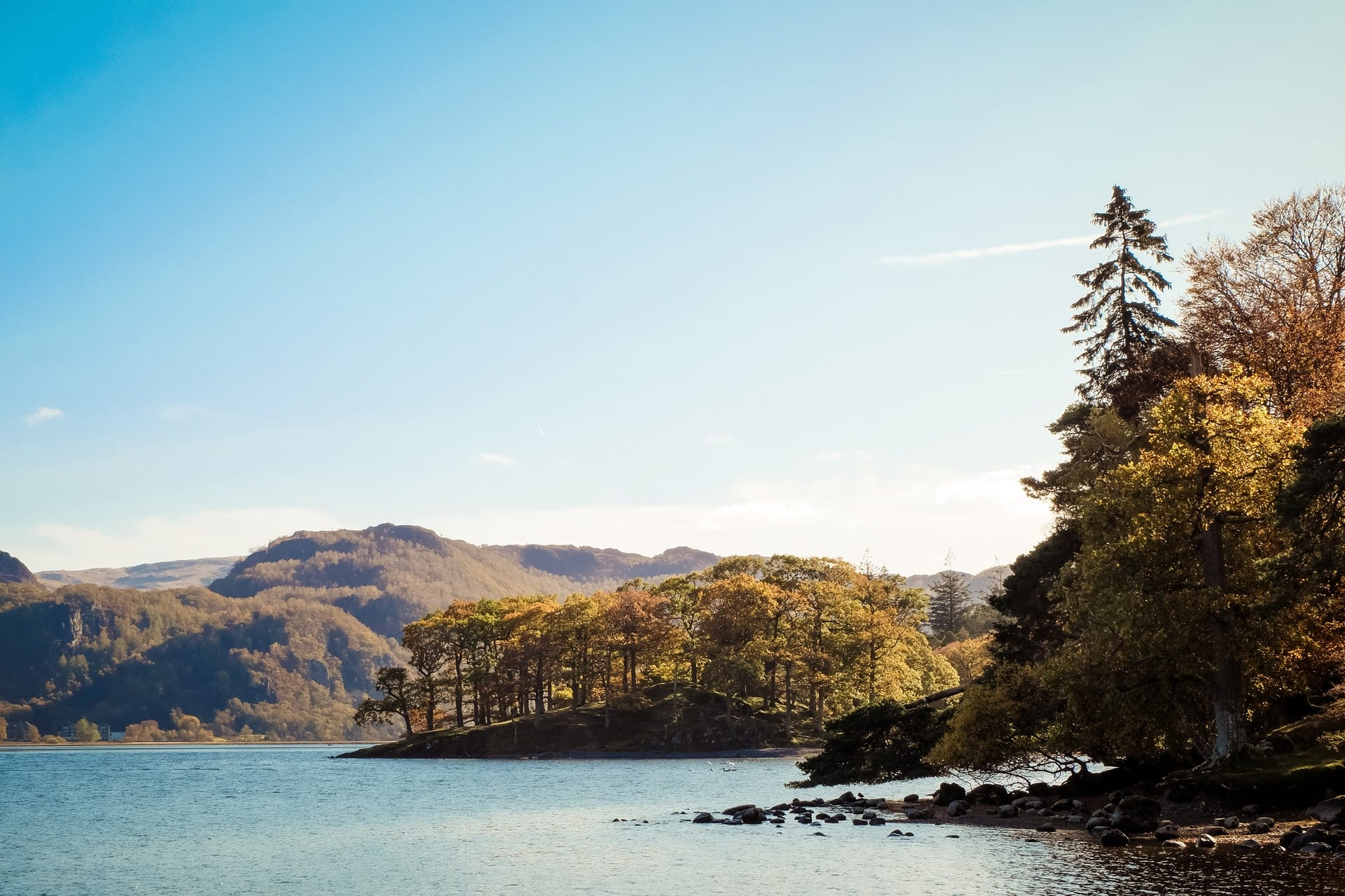 trees-and-mountains-surrounding-lake-with-blue-skies-lake-district-day-trips-from-manchester